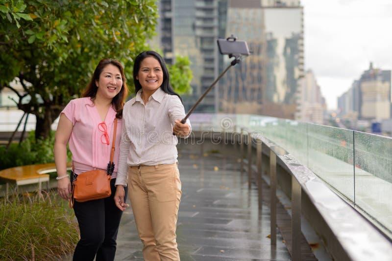 Dwa dojrzałej Azjatyckiej kobiety wpólnie przeciw widokowi miasto zdjęcie royalty free