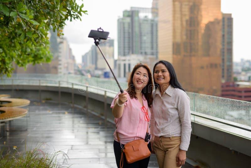 Dwa dojrzałej Azjatyckiej kobiety wpólnie przeciw widokowi miasto fotografia stock