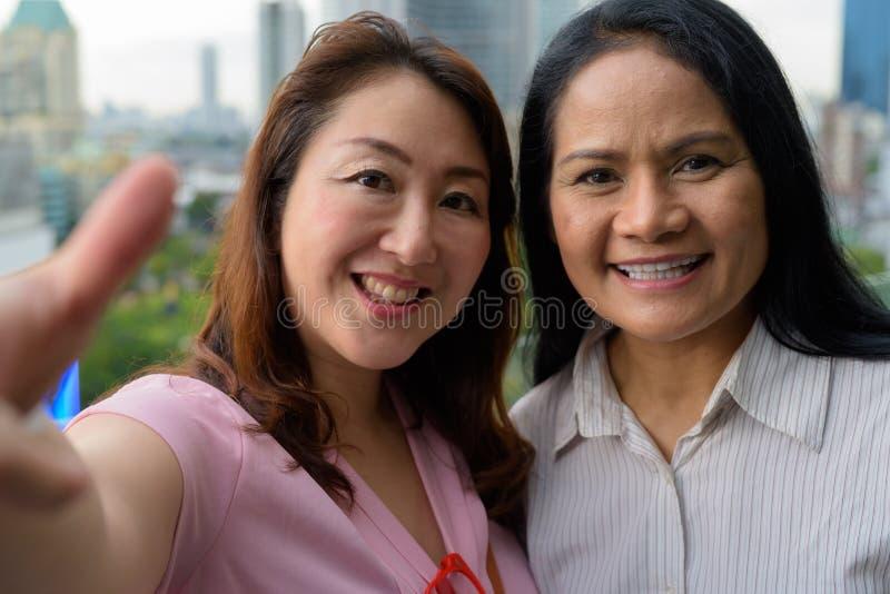 Dwa dojrzałej Azjatyckiej kobiety wpólnie przeciw widokowi miasto obrazy stock