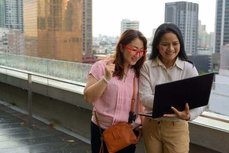 Dwa dojrzałej Azjatyckiej kobiety wpólnie przeciw widokowi miasto obraz royalty free