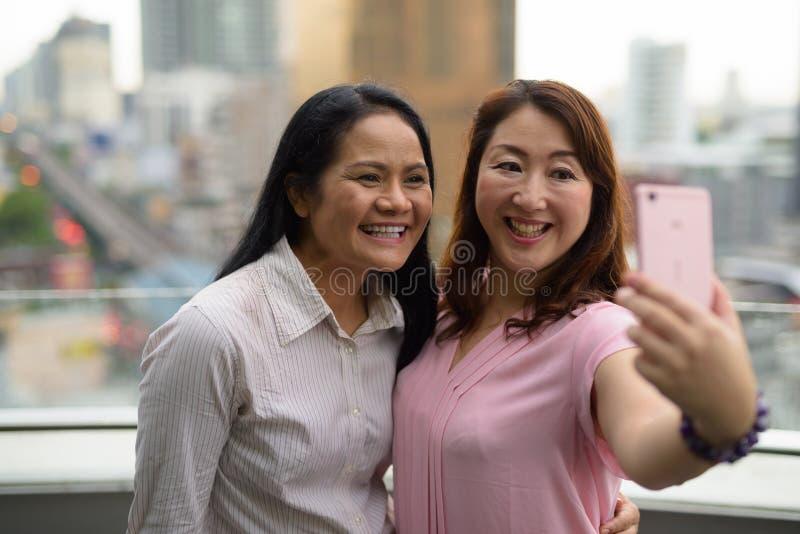 Dwa dojrzałej Azjatyckiej kobiety wpólnie przeciw widokowi miasto fotografia royalty free