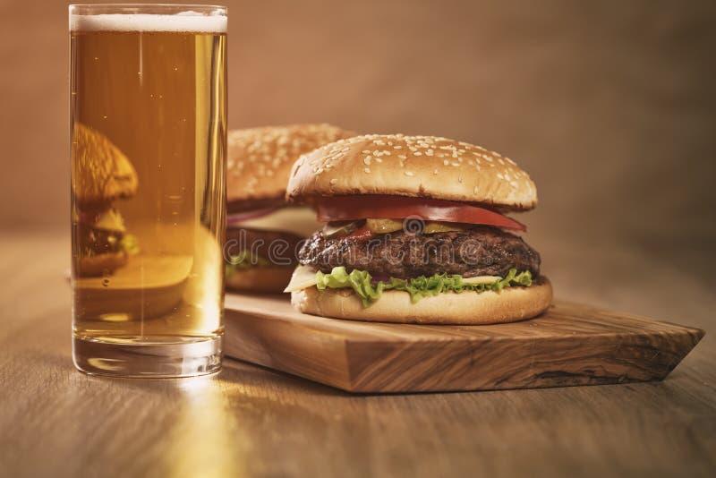 Dwa domowej roboty hamburgeru na oliwce wsiadają na dębowym stole z piwem fotografia stock
