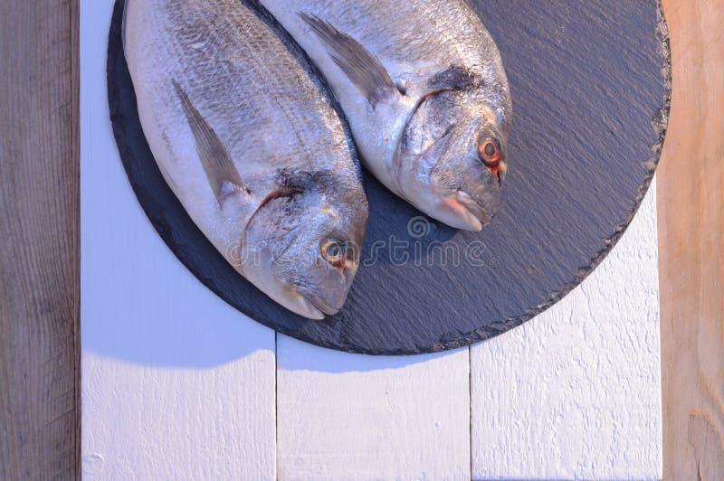 Dwa dorado ryba na czarnym talerzu fotografia stock