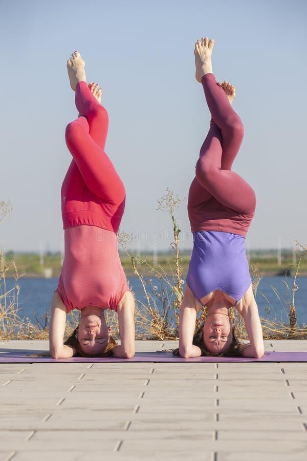Dwa dorosłej kobiety starzeli się joga outdoors w lecie w parku zdjęcie stock
