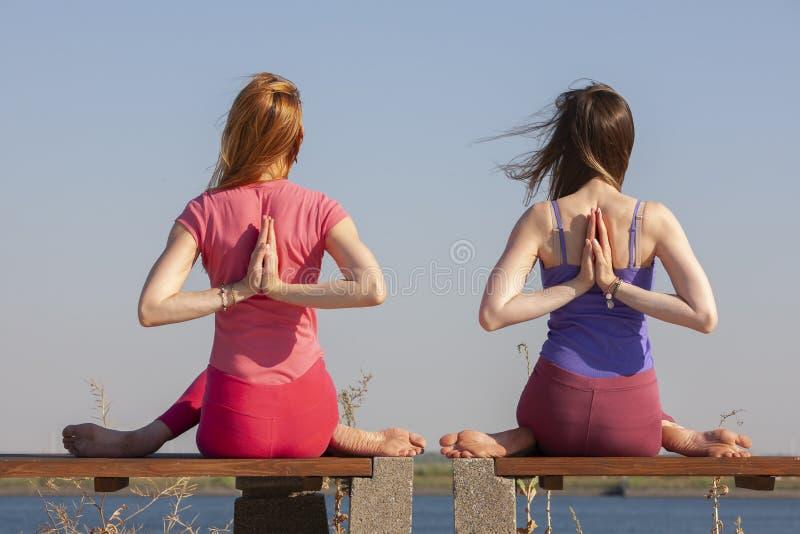 Dwa dorosłej kobiety starzeli się joga outdoors w lecie w parku obraz stock