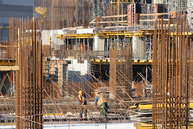 Dwa dorosłych robociarza zmory wzmacnienie na niezupełnym budynku zdjęcia stock