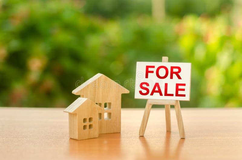 Dwa drewniane domy i stojak ze sÅ'owem SALE na tle przyrody. sprzeda? domu. Sprzedaż nieruchomoÅ›ci i nieruchomoÅ›ci zdjęcia stock