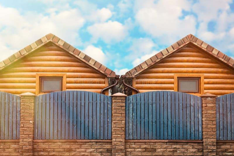Dwa drewnianego domu z b??kitn? ogrodzenie stojaka stron? strona - obok - ?wiat?o s?oneczne od nieba S?siedztwo, nowy okr?g fotografia royalty free
