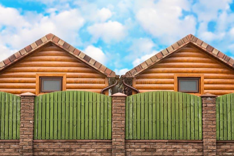 Dwa drewnianego domu z zielenieją ogrodzenie stojaka stronę strona - obok - Sąsiedztwo, nowy okręg fotografia stock
