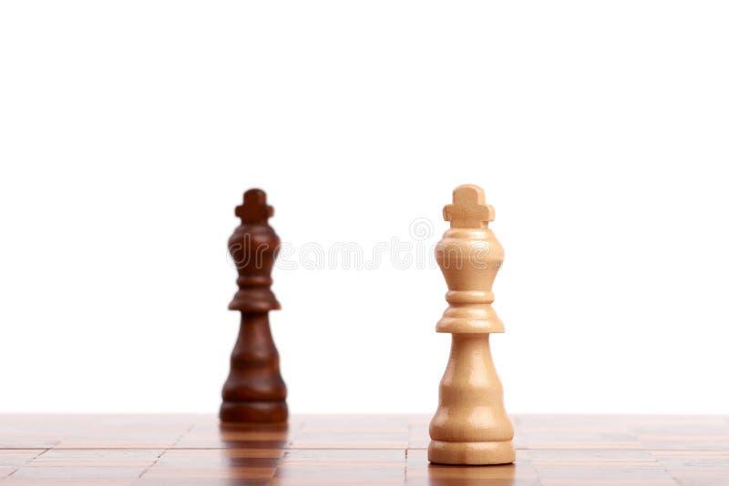 Dwa drewnianego szachowego kawałka, czarny i biały królewiątko na desce Strategia, odizolowywająca na białym tle obrazy stock
