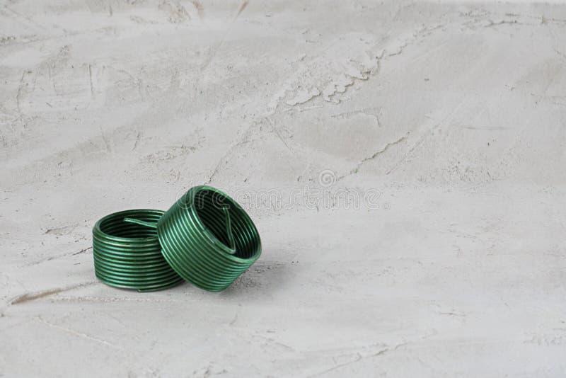 Dwa drut nici zielonej wszywki, bezpłatny bieg na popielatym cementowym tle 375 magna stal nierdzewna 04 Horyzontalny z kopii prz fotografia stock