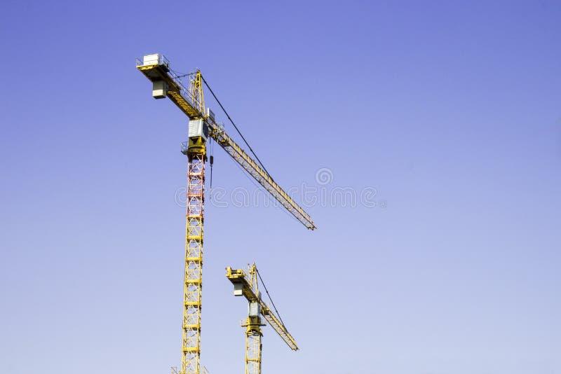 Dwa dużego żółtego budowa żurawia na niebieskiego nieba tle fotografia stock