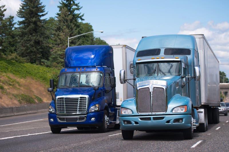 Dwa dużego takielunku semi przewożą samochodem w błękitnym brzmieniu i różnych modelach z obraz stock