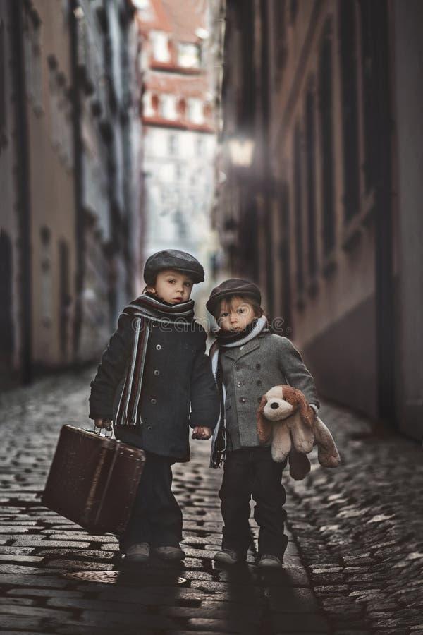 Dwa dzieci, chłopiec brata, niosący walizkę i pies zabawkę, podróżują w mieście samotnie obrazy stock