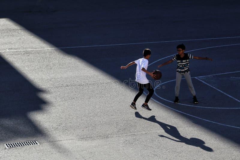 Dwa dzieci sztuki koszyk?wka na ulicznym sporta polu zdjęcia stock