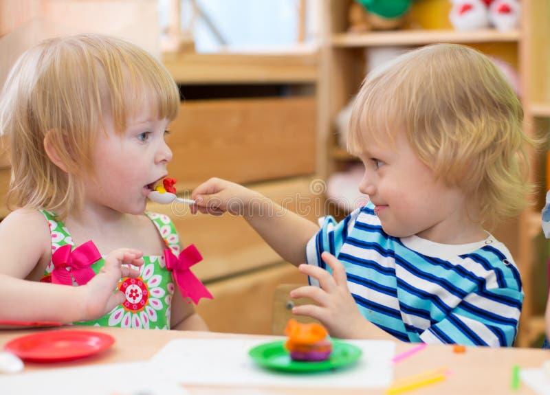 Dwa dzieciaka bawić się w dziecinu wpólnie Chłopiec żywieniowa dziewczyna fotografia royalty free