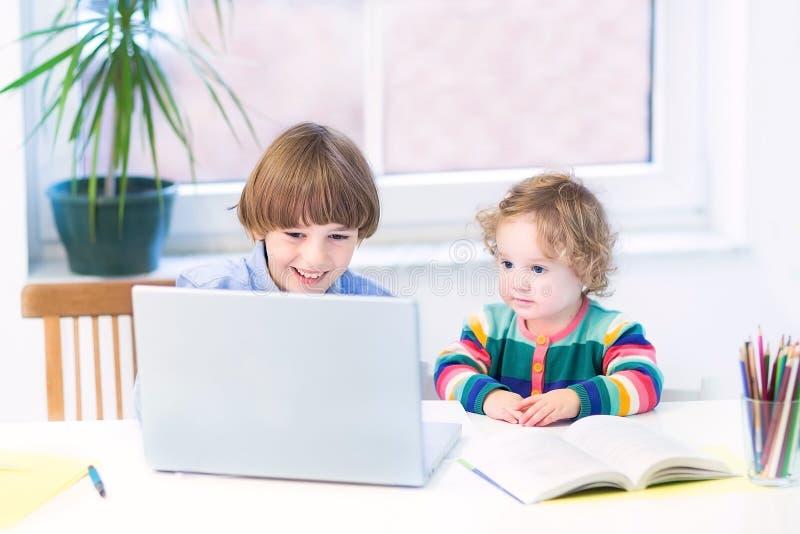 Dwa dzieciaka bawić się z laptopu obsiadaniem przy białym biurkiem obraz royalty free