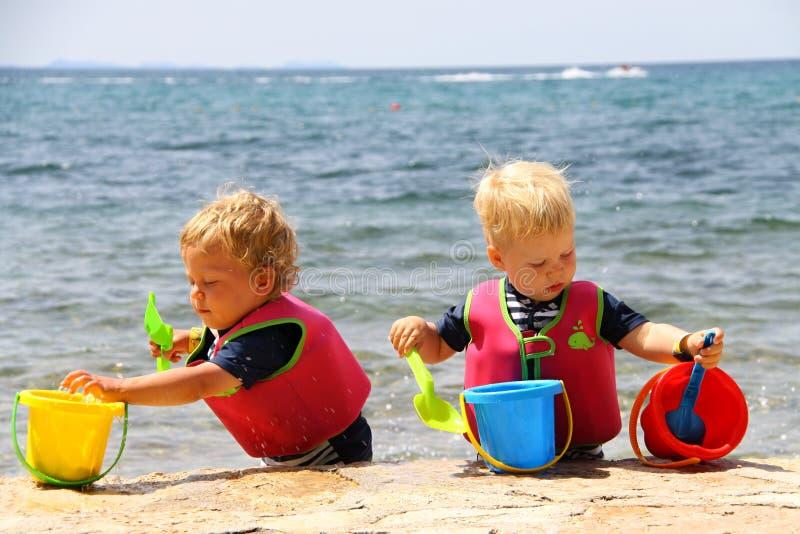 Dwa dzieciaka bawić się z wodą w pails i łopatach morzem zdjęcia royalty free