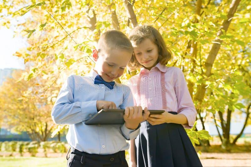 Dwa dzieciaka ogląda cyfrową pastylkę, tło jesieni pogodny park zdjęcia royalty free