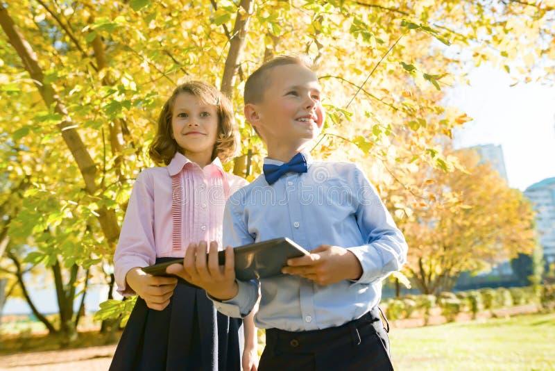 Dwa dzieciaka ogląda cyfrową pastylkę, tło jesieni pogodny park zdjęcie stock