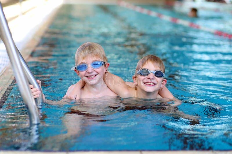Dwa dzieciaka pływa w basenie fotografia stock
