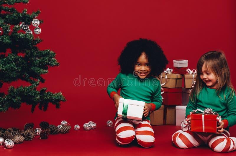 Dwa dzieciaka siedzi z ich boże narodzenie prezentami fotografia stock