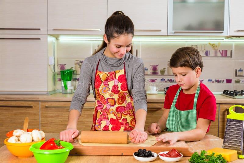 Dwa dzieciaka ugniata ciasto, robi pizzy fotografia stock