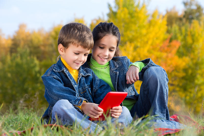 Dwa dzieciaka z pastylka pecetem obrazy royalty free
