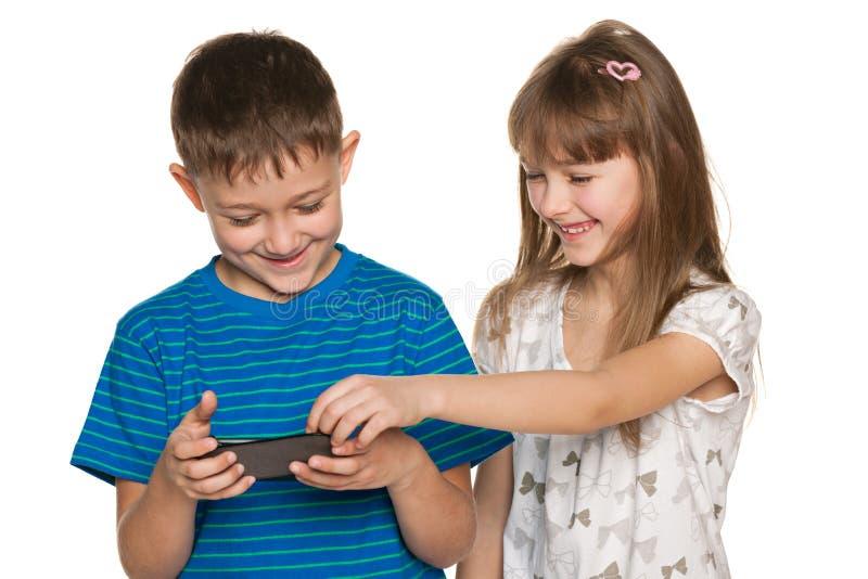 Dwa dziecka plaing z smartphone zdjęcia stock