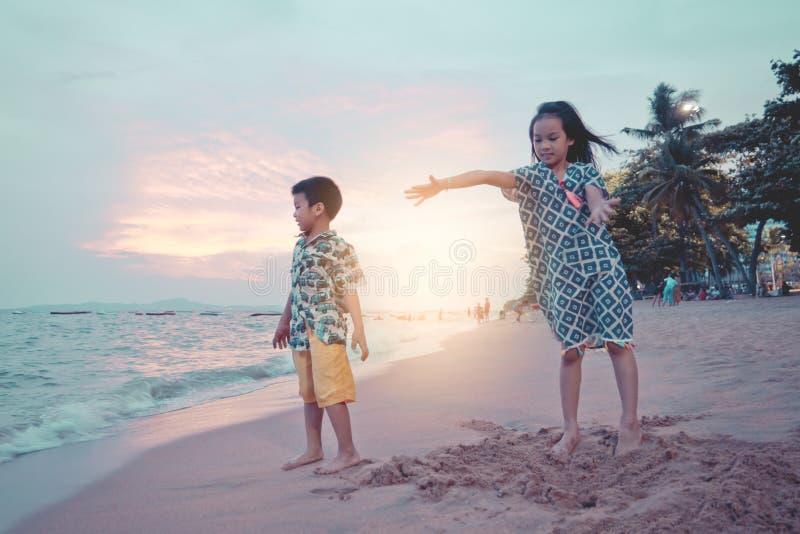 Dwa dziecka bawi? si? z fal? i piaskiem w Pattaya pla?y Tajlandia fotografia stock