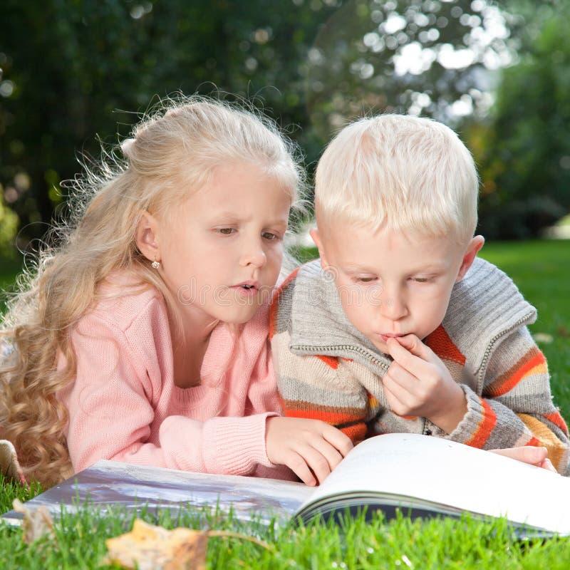 Dwa dziecka czytają książkę na gazonie zdjęcia royalty free