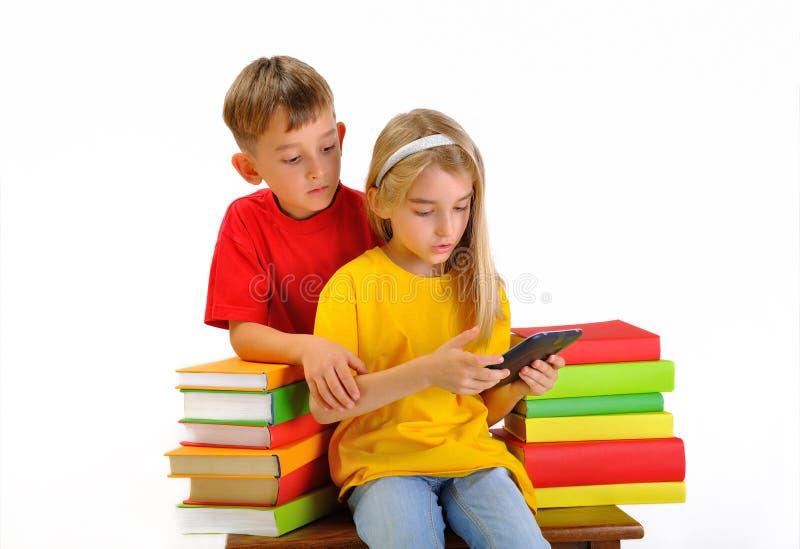 Dwa dziecka czytającego ebook otaczającego książkami obraz stock