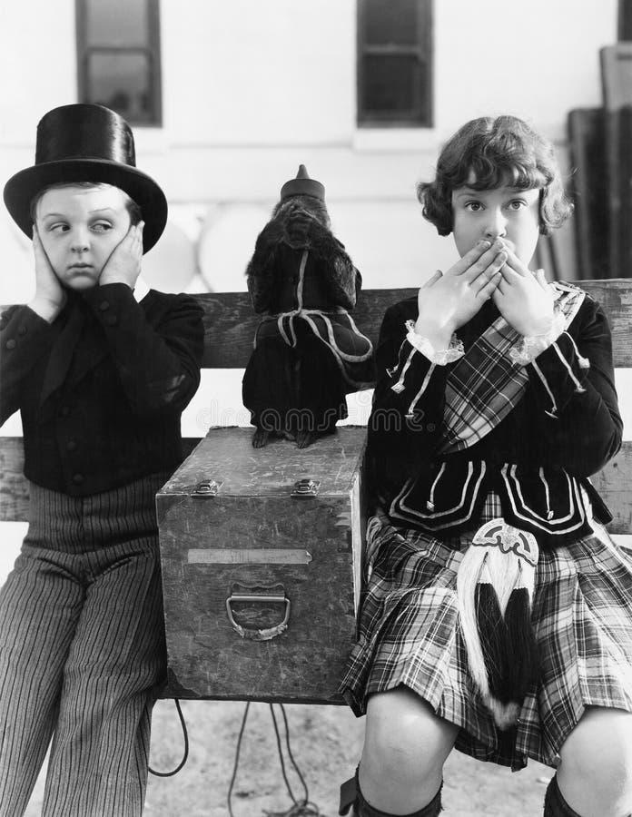 Dwa dziecka i małpiego bawić się słuchają żadny zło, widzią żadny zło, mówją żadny zło (Wszystkie persons przedstawiający no są d obraz stock
