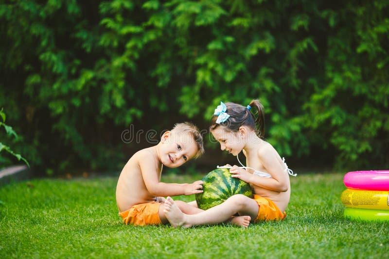 Dwa dziecka Kaukaski brat i siostra, siedzi na zielonej trawie w podwórko dom i ściska dużego smakowitego słodkiego arbuza, obraz royalty free