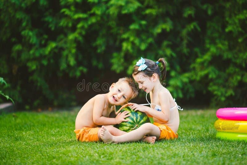 Dwa dziecka Kaukaski brat i siostra, siedzi na zielonej trawie w podw?rko dom i ?ciska du?ego smakowitego s?odkiego arbuza, zdjęcie royalty free