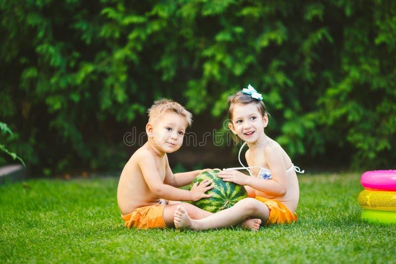 Dwa dziecka Kaukaski brat i siostra, siedzi na zielonej trawie w podw?rko dom i ?ciska du?ego smakowitego s?odkiego arbuza, obrazy royalty free