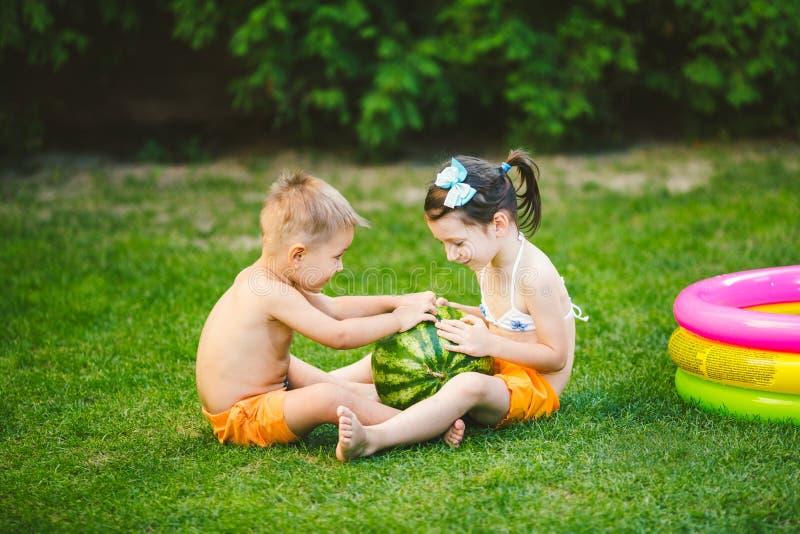 Dwa dziecka Kaukaski brat i siostra, siedzi na zielonej trawie w podw?rko dom i ?ciska du?ego smakowitego s?odkiego arbuza, fotografia royalty free