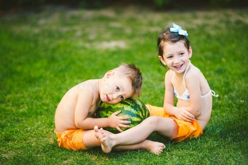 Dwa dziecka Kaukaski brat i siostra, siedzi na zielonej trawie w podw?rko dom i ?ciska du?ego smakowitego s?odkiego arbuza, obraz royalty free