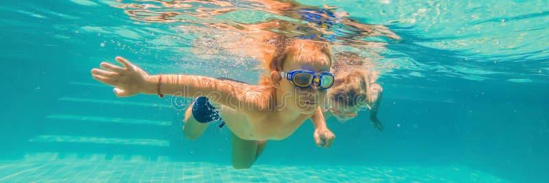 Dwa dziecka nurkuje w maskach podwodnych w basenu sztandarze, długi format obraz royalty free
