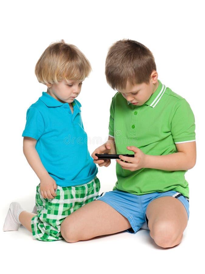 Dwa dziecka plaing z smartphone fotografia stock