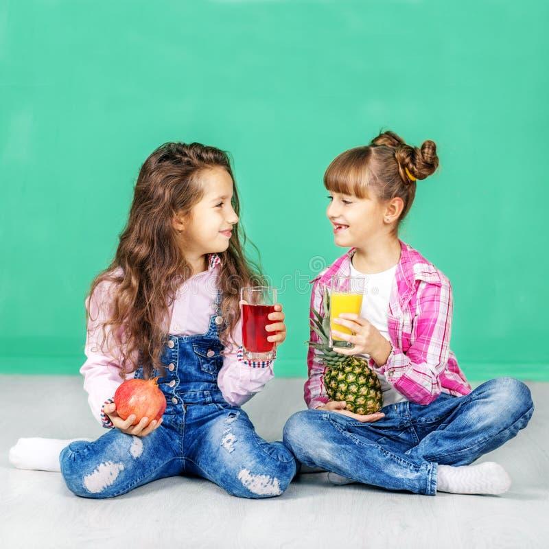 Dwa dziecka są opowiadający soki i pijący kwadrat Dziewczyny z fotografia royalty free