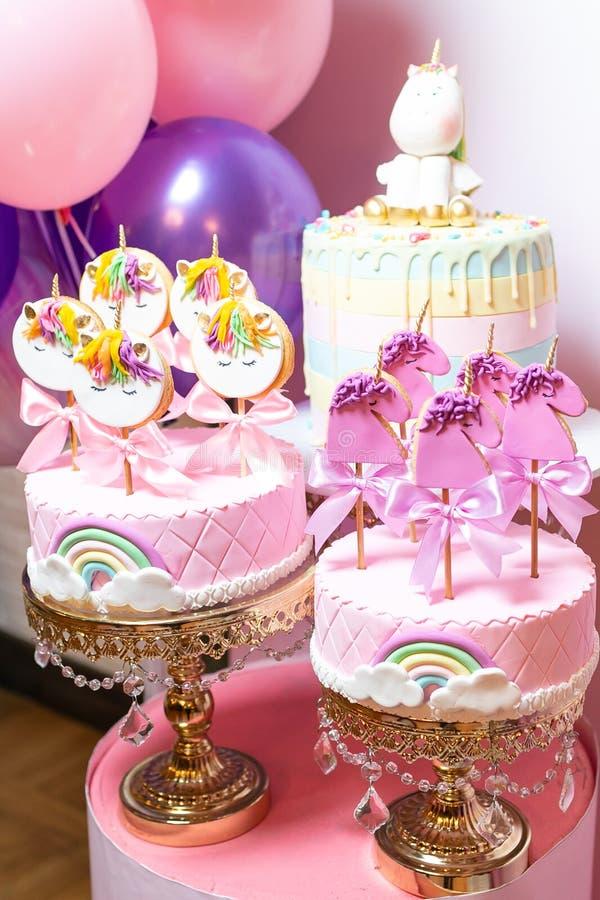 Dwa dziecka tortowego z marcepanami, z tęczą, biel chmurami i ciastkami na kijach, w formie jednorożec obrazy royalty free