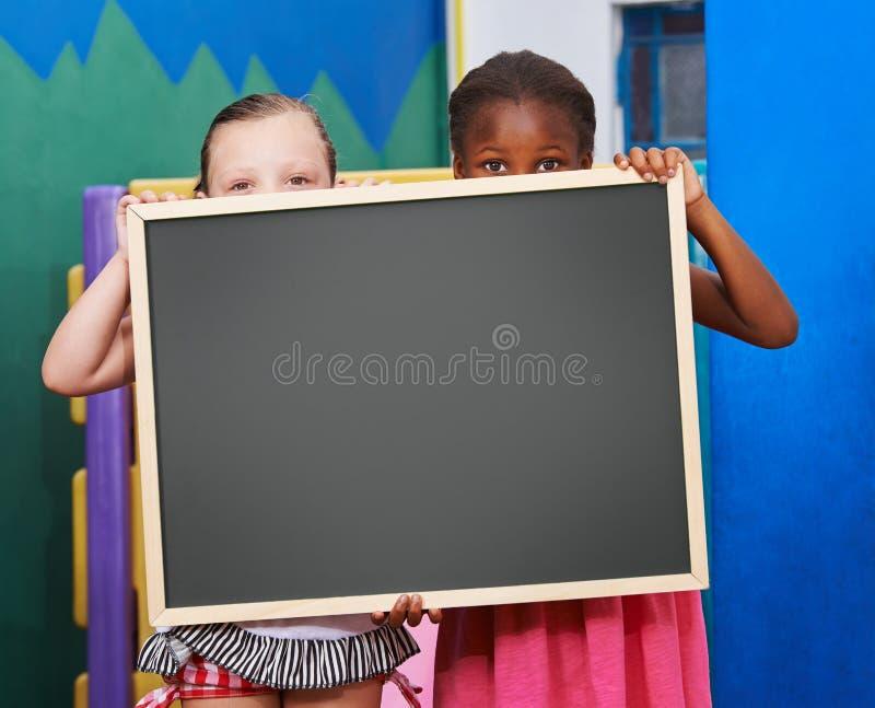 Dwa dziecka trzyma blackboard w preschool zdjęcia stock