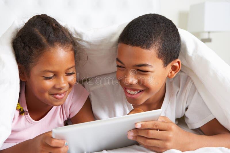 Dwa dziecka Używa Cyfrowej pastylkę Pod Duvet obraz stock