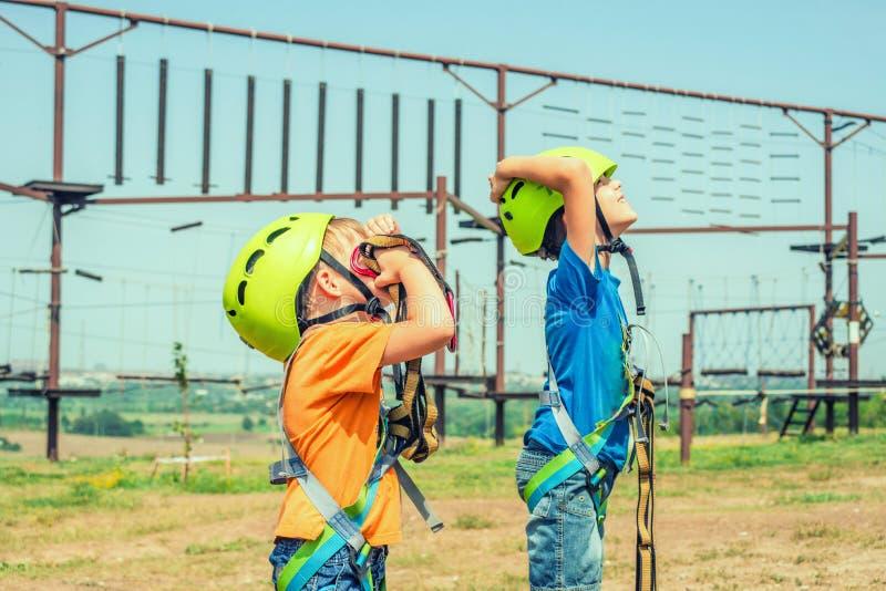 Dwa dziecka w hełmach i zbawczej przekładnia są przyglądający w górę ekstremum parka wewnątrz zdjęcia royalty free