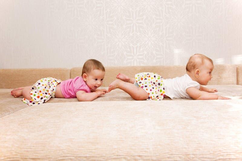 Dwa dziecko bliźniaka czołgać się jeden po inny zdjęcia stock