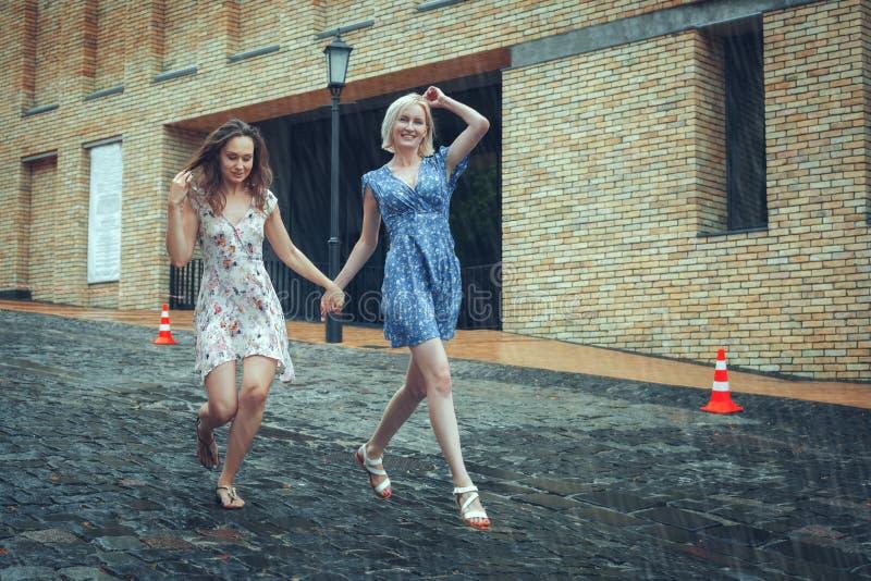 Dwa dziewczyn bieg w deszczu zdjęcia stock