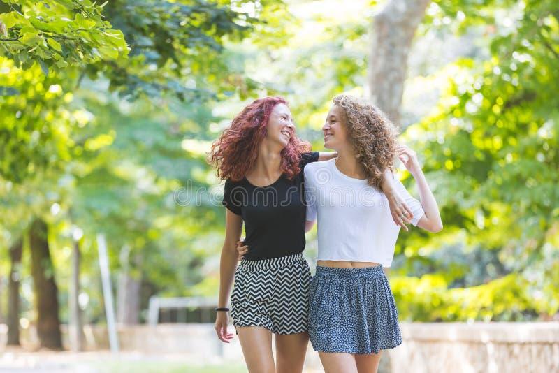 Dwa dziewczyn chodzić obejmuję przy parkiem obraz royalty free