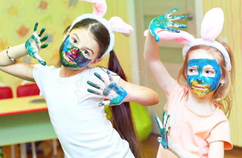 Dwa dziewczyn mała śmieszna farba barwił farbę na jego twarzy obraz stock