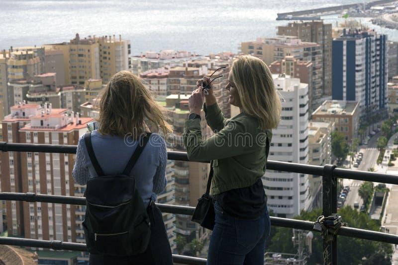 Dwa dziewczyn stojak na wzgórzu i spojrzenie przy piękną panoramą Hiszpański miasto Malaga na ciepłym fotografia royalty free